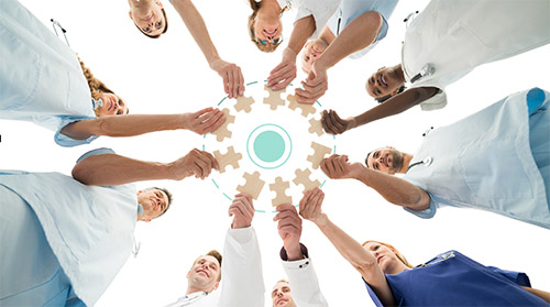 clinical group in circle with each person holding a puzzle piece